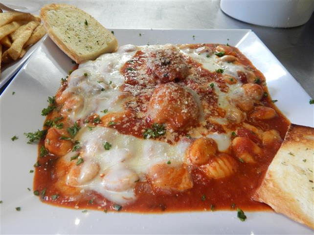 gnocchi entree dish with pasta, cheese, herbs and meatballs with a side of garlic bread
