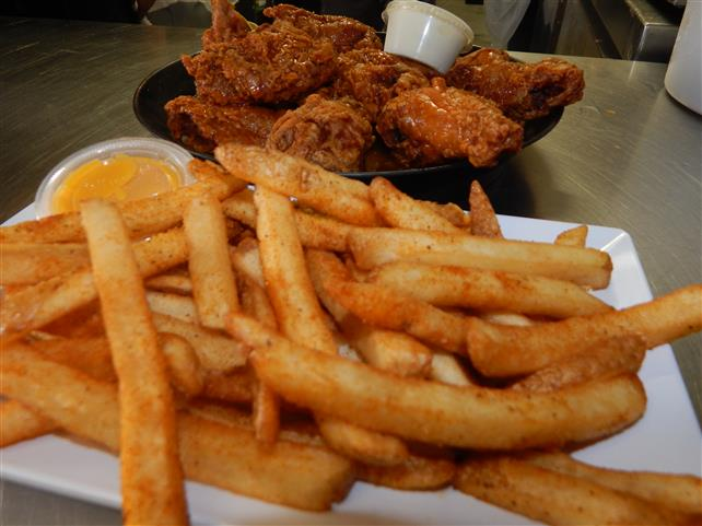 plate of buffalo chicken wings and a side plate of french fries