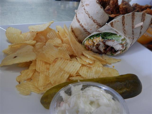 fried chicken wrap with cheese and lettuce with a side of chips, coleslaw and a pickle spear