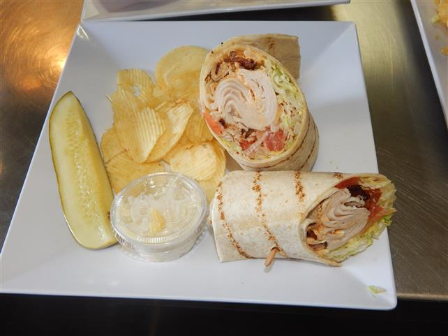 turkey club wrap with bacon and a side of chips with coleslaw and a pickle spear