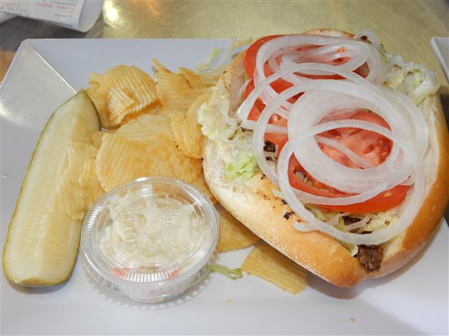 gyro on a roll topped with lettuce, tomatoes and onions with a side of chips, coleslaw and a pickle spear
