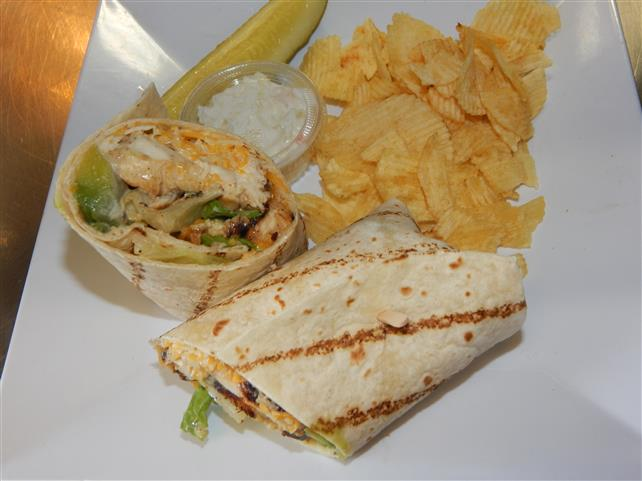 grilled chicken wrap with cheese and avocado with a side of chips, coleslaw and a pickle spear