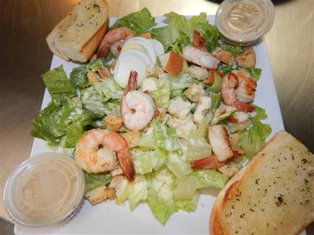 salad topped with cooked shrimp, eggs and croutons with garlic bread on the side