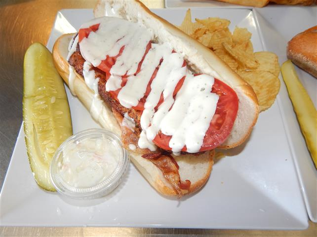 gyro on a sub topped with tomatoes and sauce with a side of chips, coleslaw and a pickle spear