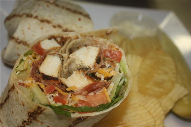 grilled chicken wrap with cheese, lettuce, tomatoes and bacon with a side of chips, coleslaw and a pickle spear