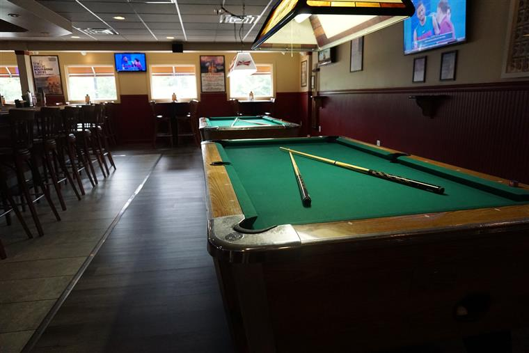 interior pool table next to the bar with stools