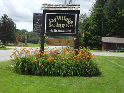 outdoor signage next to a road with the jay village logo on it