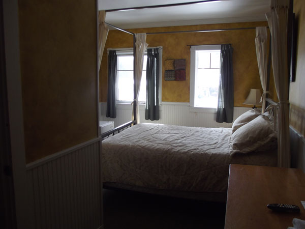 suite with a large bed with a bed frame with curtains