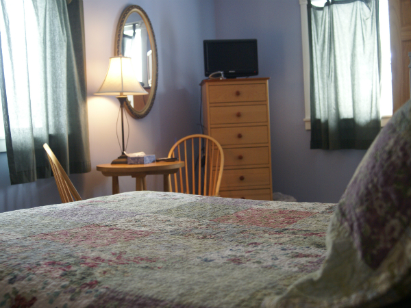 suite with a large bed, a small table with chairs and a dresser with a flat screen tv on top