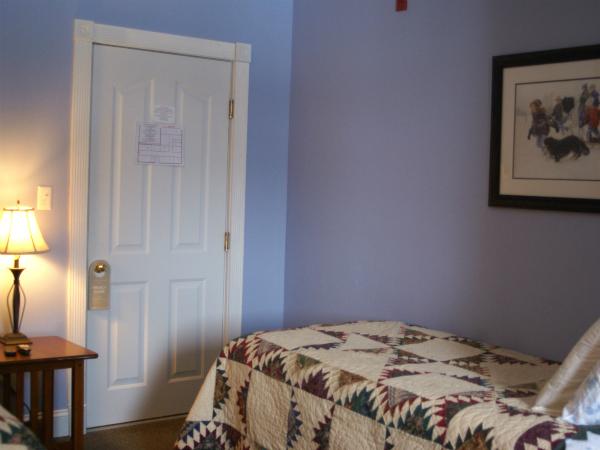 suite with a large bed and a decorative picture hanging on the wall
