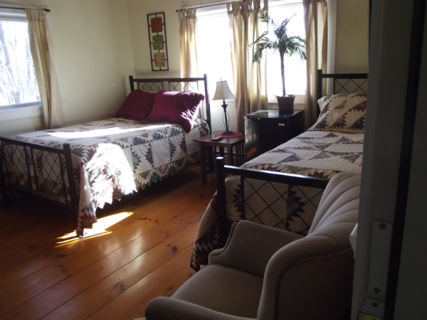 suite with a queen bed and twin beds and a chair