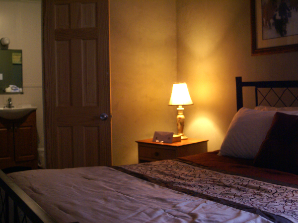 suite with a large bed, a night stand with a lamp and a decorative painting hanging on the wall