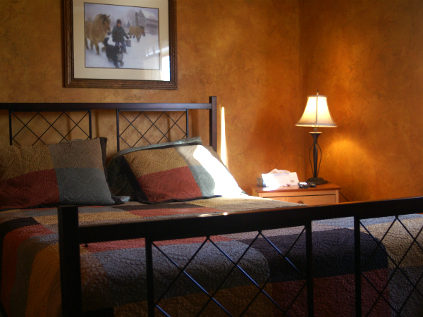 suite with a large bed next to a night stand with a lamp  and a decorative picture hanging on the wall