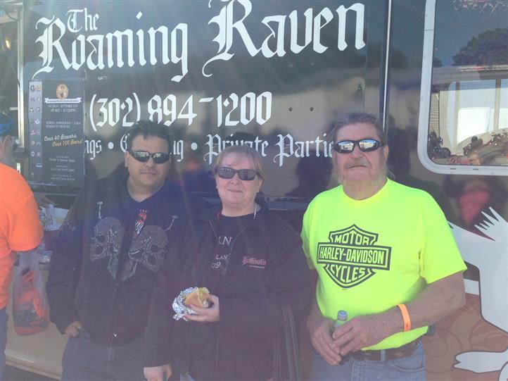group of customers in front of the roaming raven food truck smiling for the camera