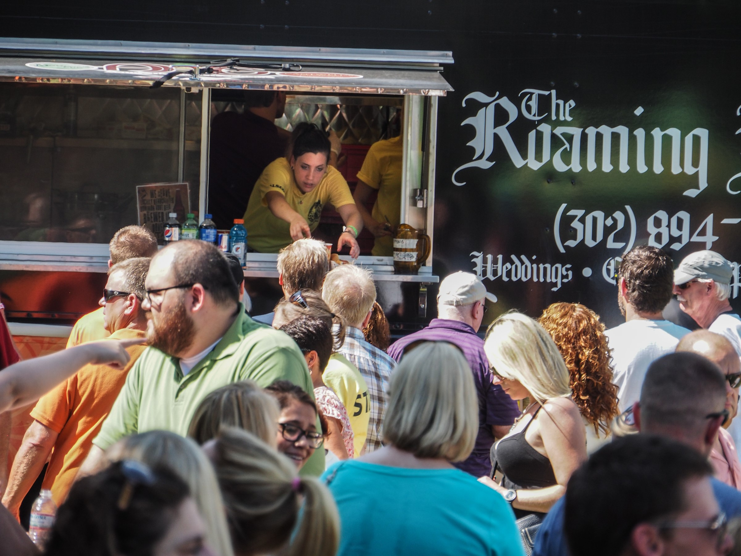 large crowd gathered just outside the window of the roaming raven food truck