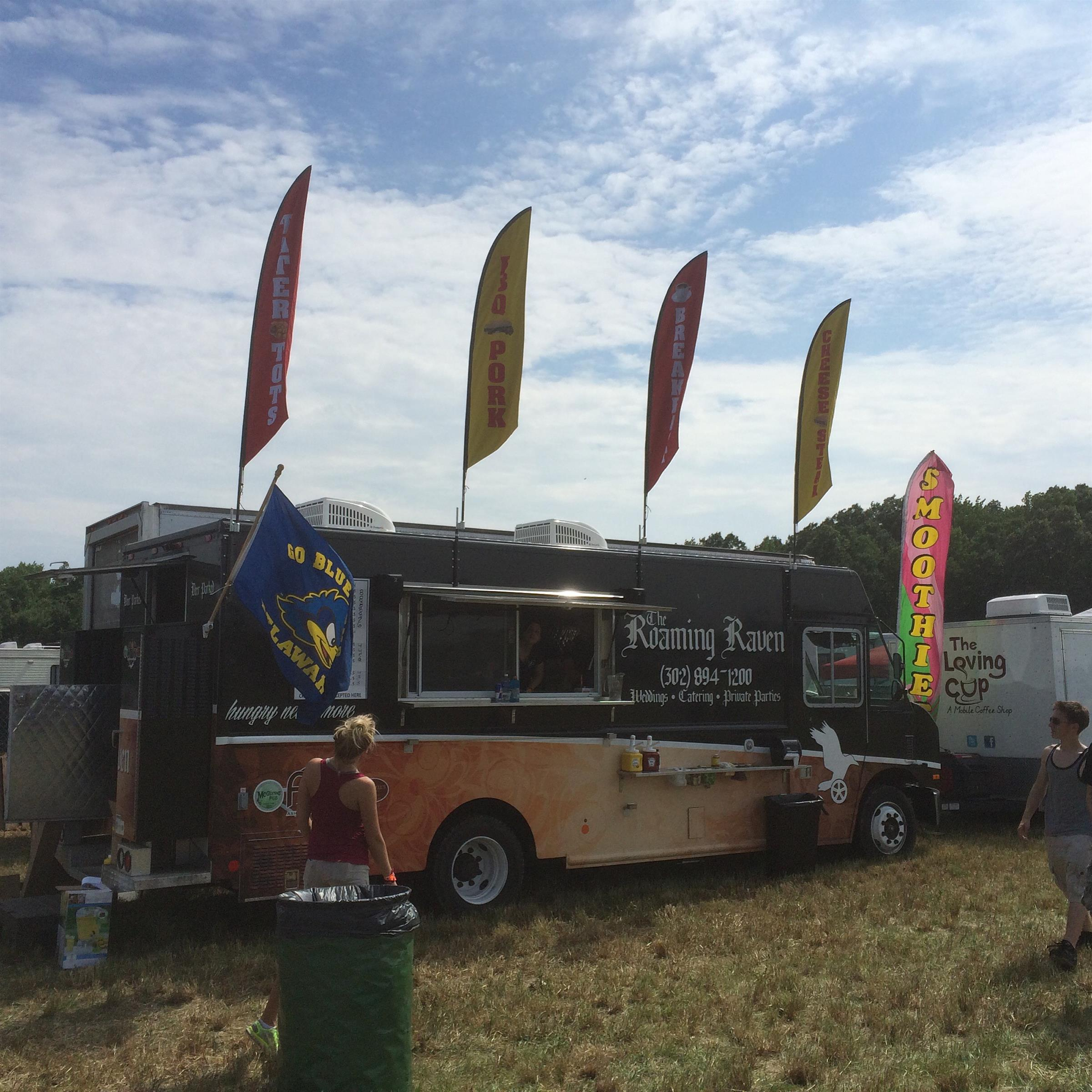 the roaming raven food truck at an outdoor event with flags on top