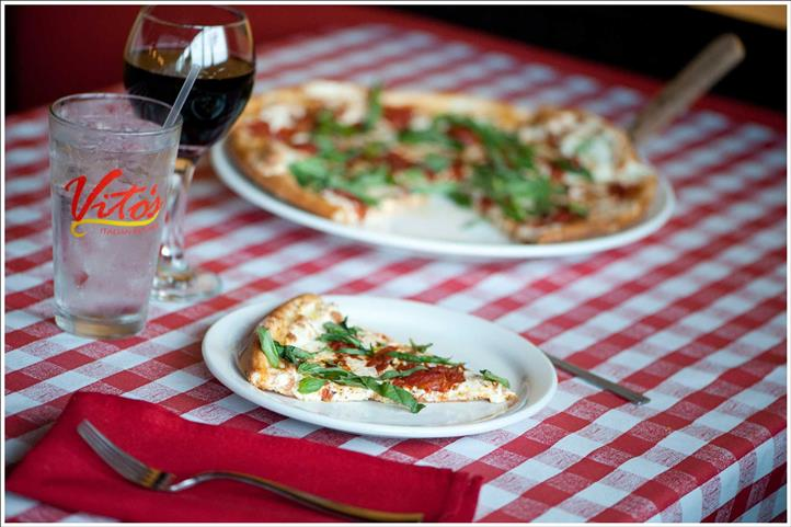 Pizza with tomatoes, mozzarella, spinach on dish next to pie with the same. Water and wine glass adjacent.
