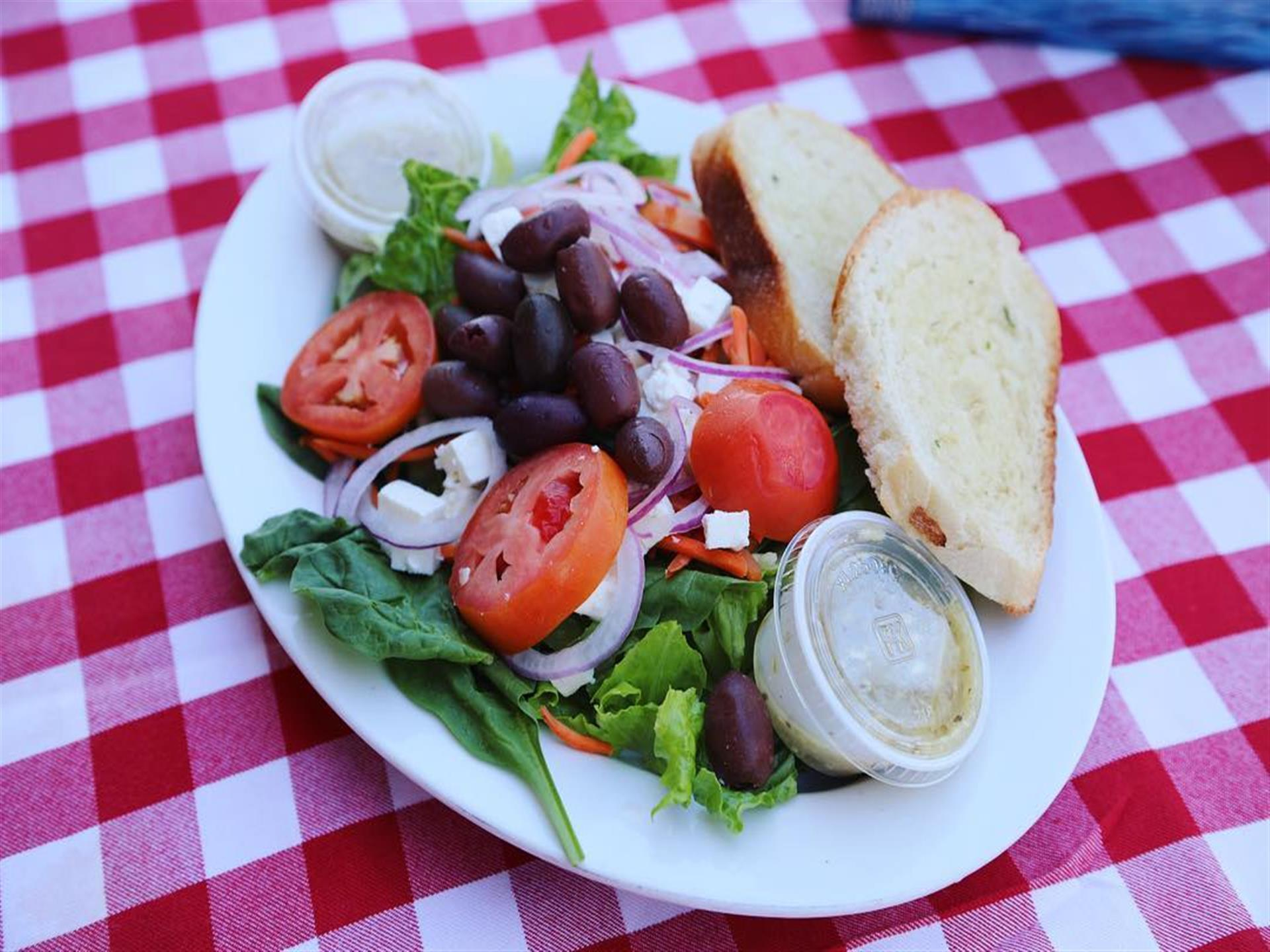 Salad with feta cheese, tomatoes, olives, side of dressing and bread.