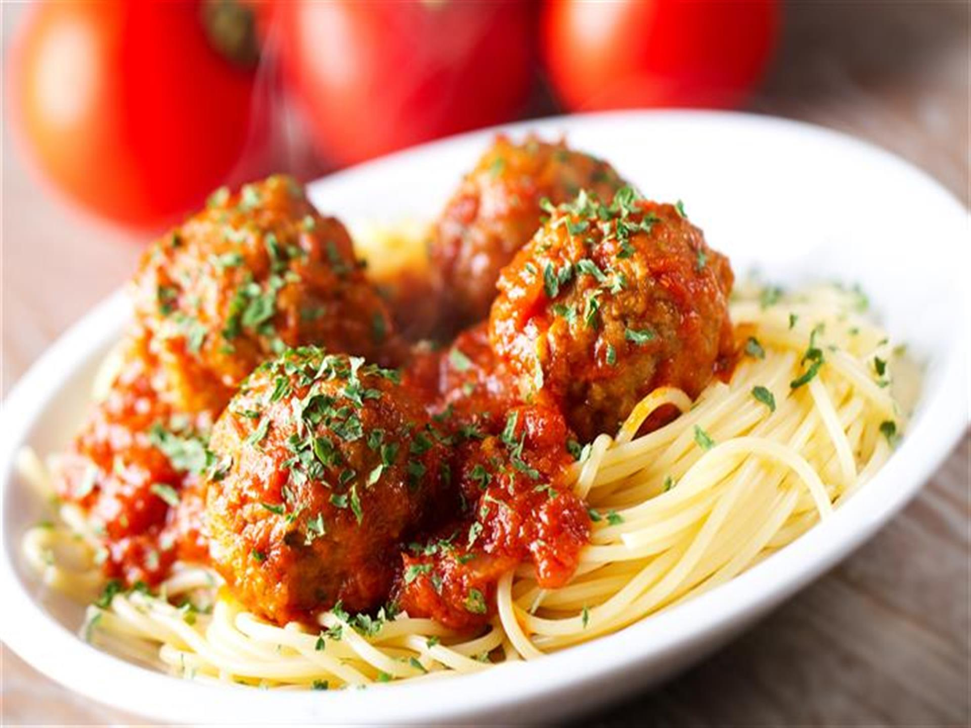 Spaghetti and meatballs with whole tomatoes in background