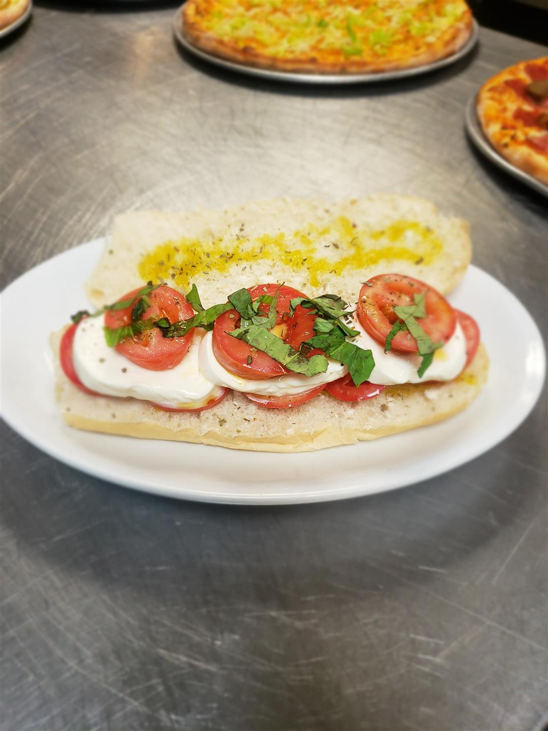 Extra virgin olive oil, whole-peeled tomatoes, fresh mozzarella, basil and oregano on a roll