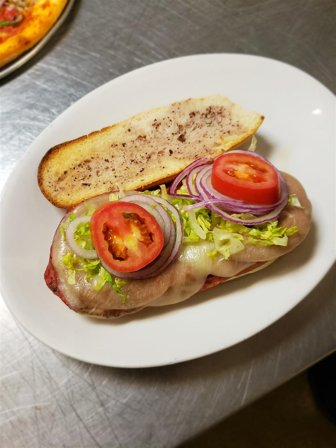 Salami, capicola, ham, provolone, oil and vinegar, lettuce, tomato and onion on a roll