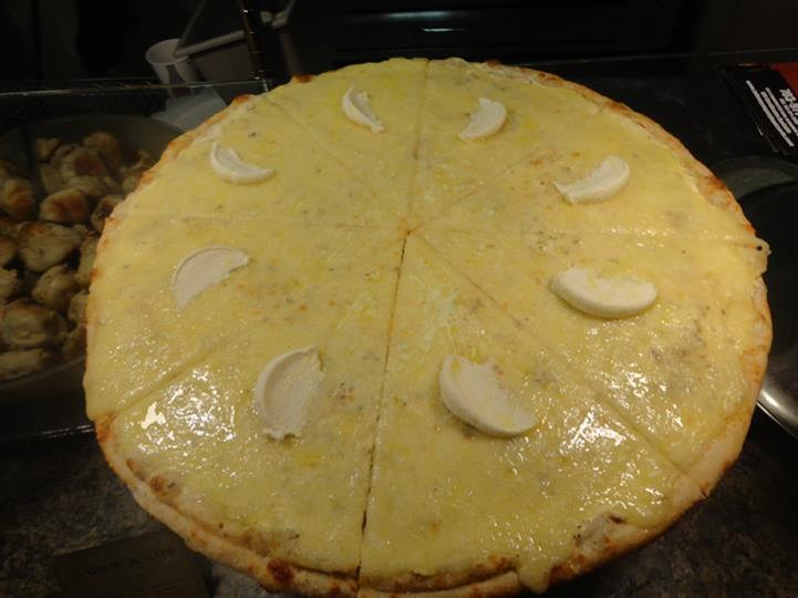 large cheese pizza with mozzarella slices on top