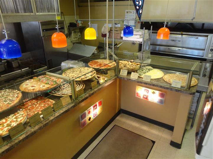 front counter with various types of pizza being displayed