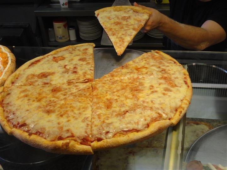 large cheese pizza with a person taking a slice