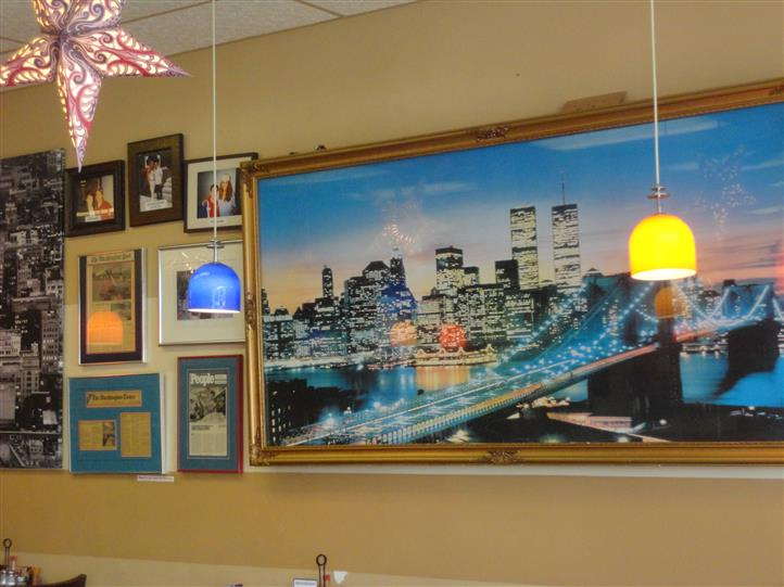 various pictures of new york framed on the inside walls