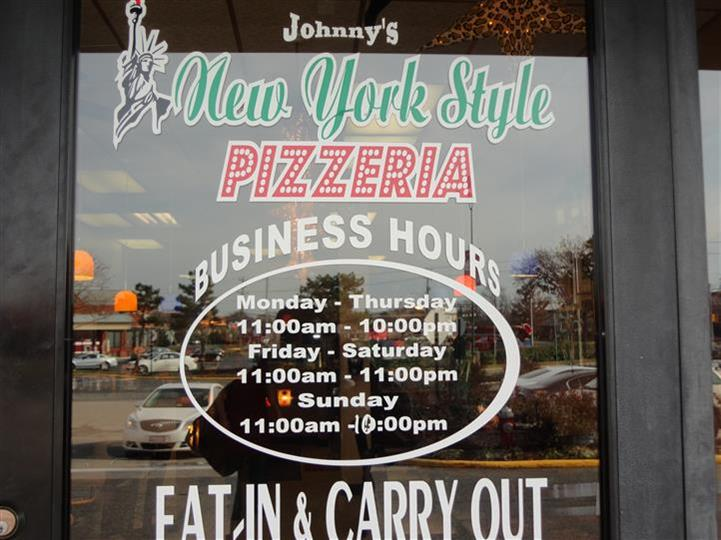 signage on the front store with johnny's new york style pizzeria logo and their business hours