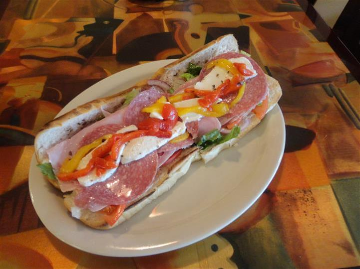 italian hero with meats, lettuce, tomatoes, peppers and mozzarella cheese