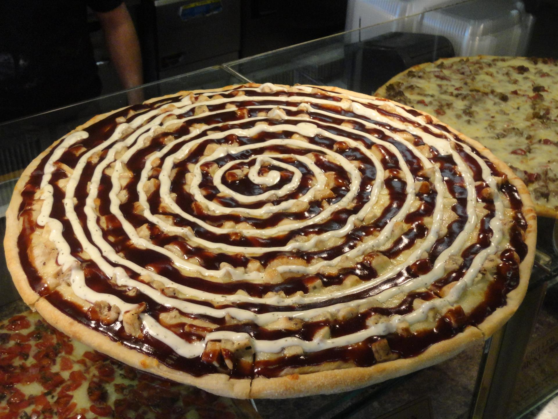 Pizza pie with a spiral drizzle and toppings