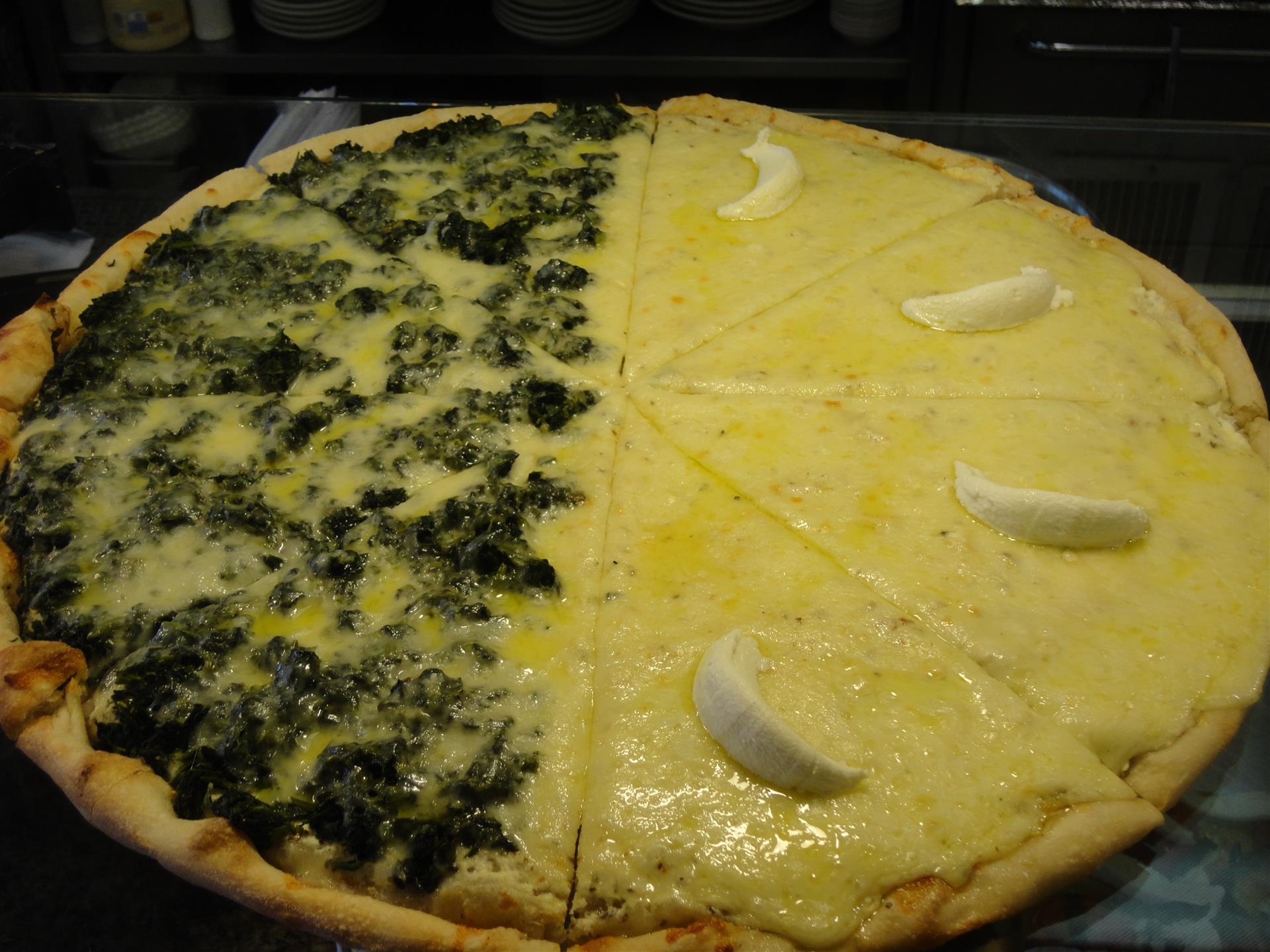 Pizza with half spinach and half white cheese pie