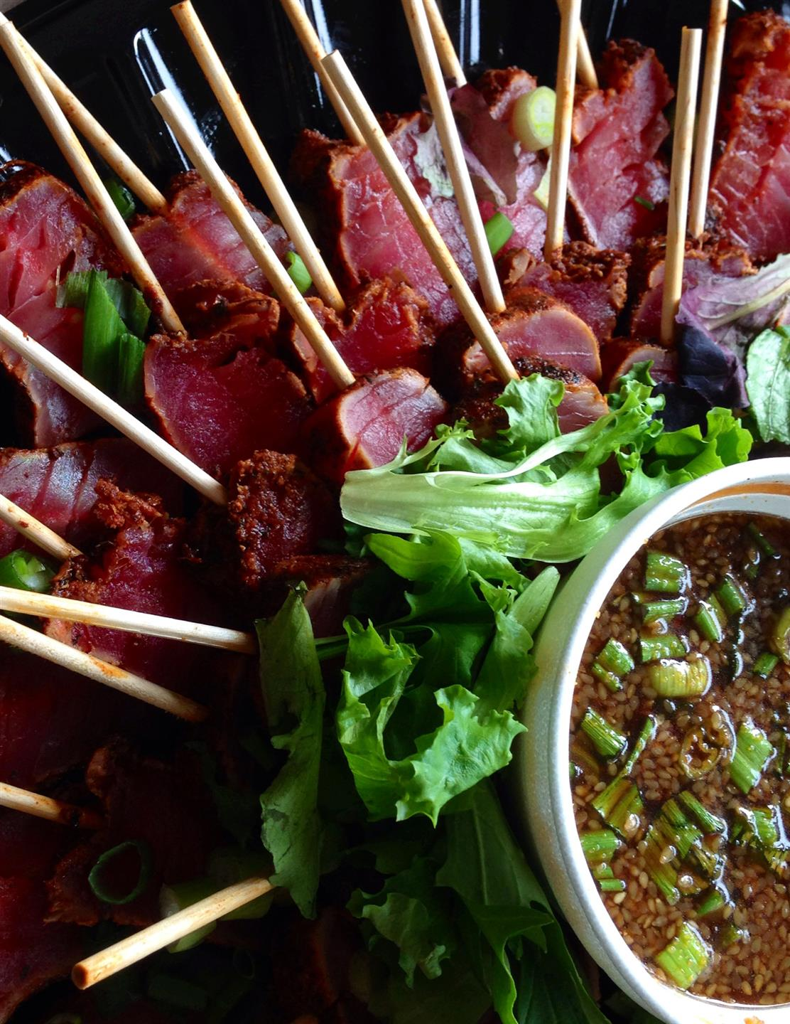 catering display of tuna on skewers topped with greens and sauce on the side