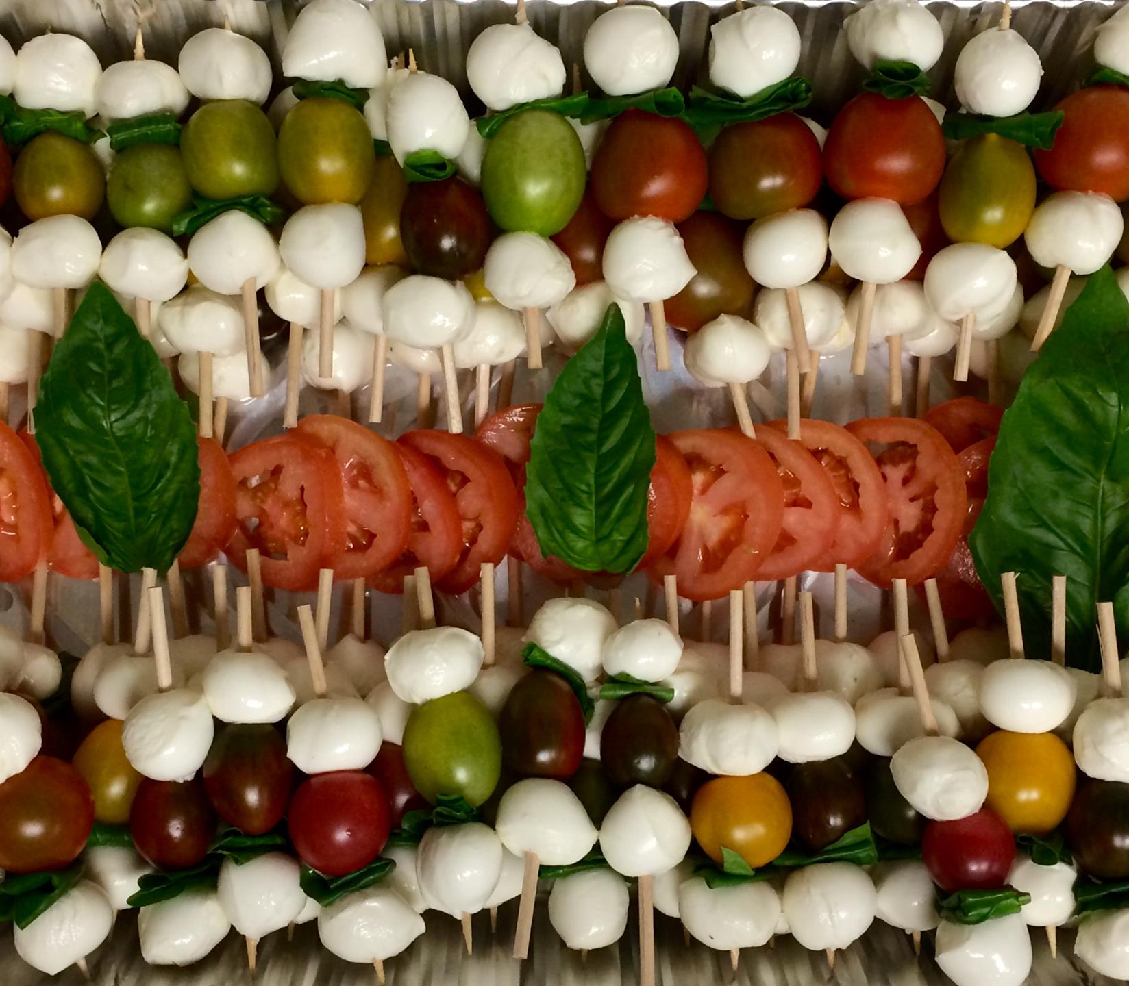 catering display of tomatoes and mozzarella on skewers topped with basil leaves