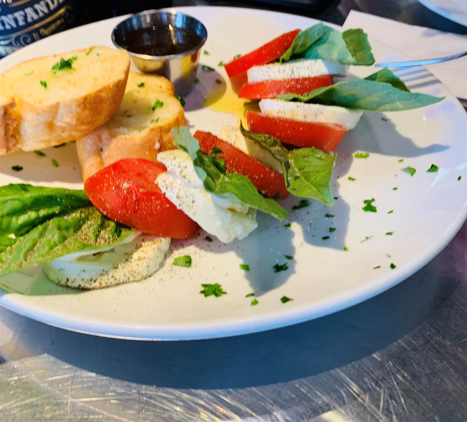 Mozzarella di bufala, Roma tomato, basil, extra virgin olive oil and balsamic vinegar on a plate