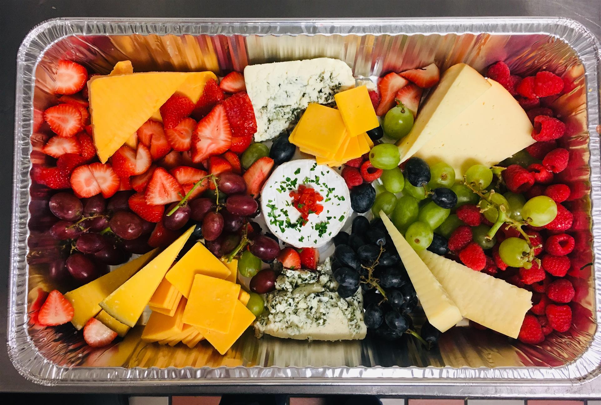 A foil tray filled with Strawberries, Grapes, Blueberries, Raspberries and assortment of Cheese