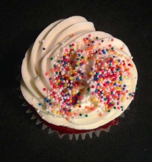 Cupcake with vanilla frosting and multi-colored sprinkles