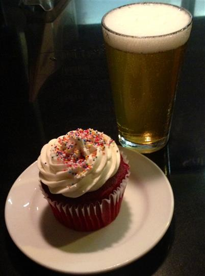 Cupcake with vanilla frosting and multi-colored sprinkles next to beer in full glass