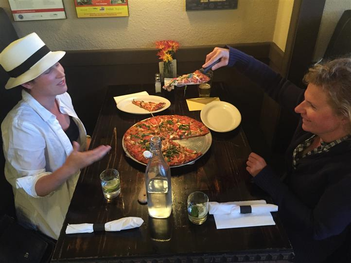 Two people enjoying pizza pie at dining table