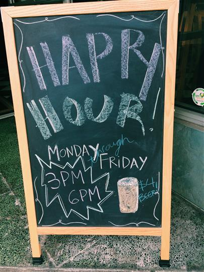 Chalkboard sign for Happy Hour, monday through friday 3 PM to 6 PM