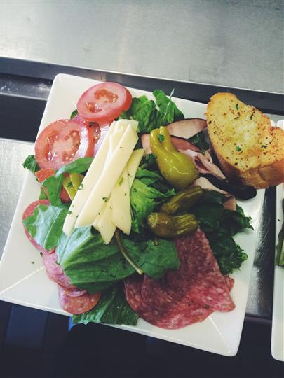 Antipasti. Cured meat, tomatoes, cheese, pepperoncini, garlic bread, greens