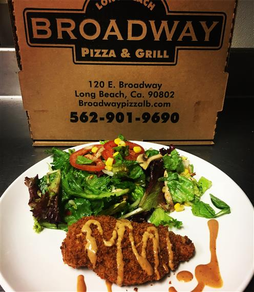 Broadway pizza and grill pizza box behind entree with salad.