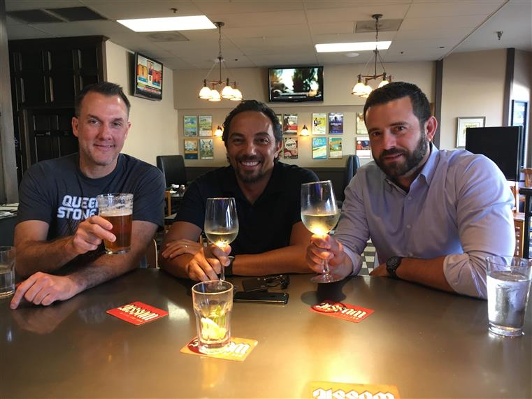 Three men sitting and holding beer and wine glasses, posing for photo.