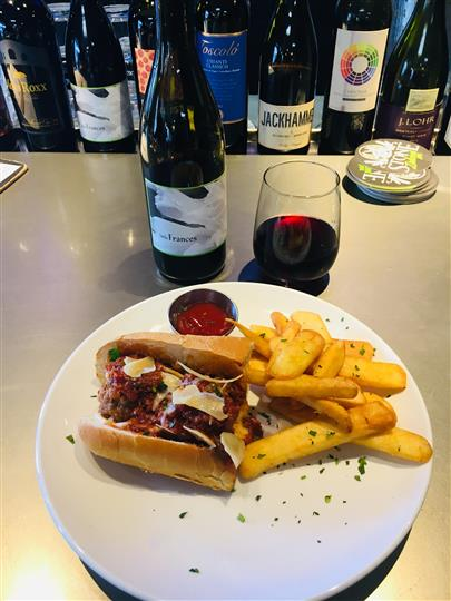 House made meatball sandwich with steak fries, red wine bottle and glass.