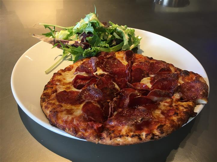 8 inch personal pepperoni pizza with side of greens on dish.