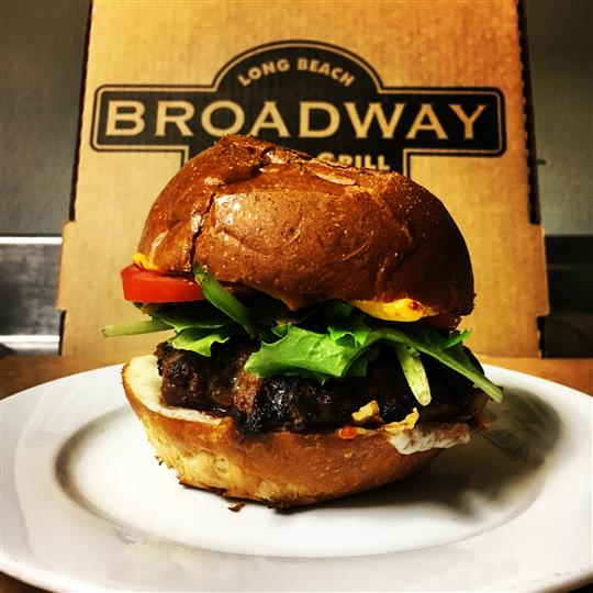 The Bar Burger in front of Broadway Pizza & Grill pizza box. 1/2 lb. ground Angus chuck, spring greens, Roma tomato, American cheese, provolone cheese, flash fried onions and Broadway sauce, served on a brioche roll.