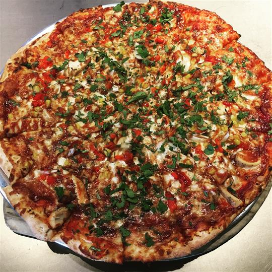 B B Q Chicken pizza. Mozzarella, grilled chicken, BBQ sauce, roasted red peppers, onions, corn and fresh cilantro.