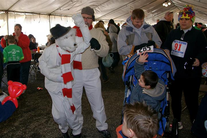 Person in polar bear costume air high fiving toddler