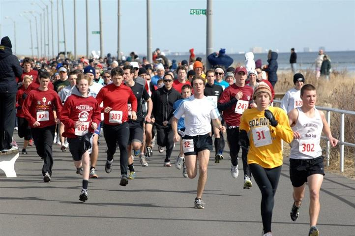 Marathon runners alongside the shore
